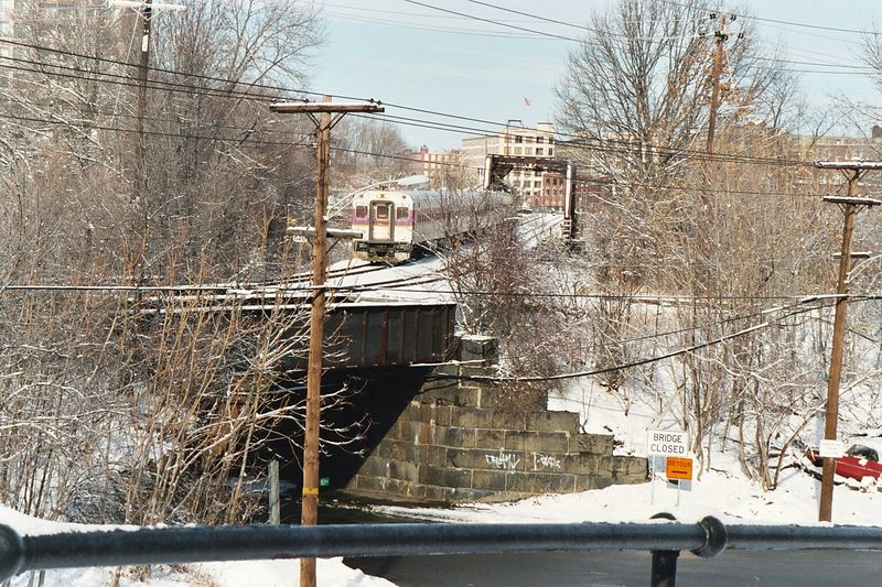 The control car of an MBTA commuter train has just crossed the Merrimack River Bridge and is about to make a stop at Bradford. Bradford is a section of Haverhill, Mass. and is located on the former Western Route Main Line of the B&M' s Portland Division. The abandoned roadbed on the right used to be B&M's Georgetown Branch.