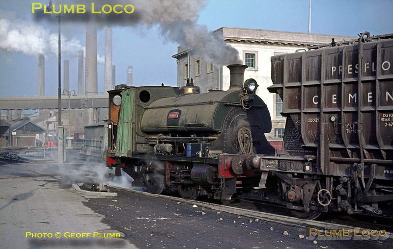 """Peckett 0-4-0ST """"Thor"""" (Class R2 No. 1689/1925) is about to traverse the level-crossing over the road into the Tunnel Cement works at Purfleet, Essex, having brought a train of Presflo Cement wagons from the interchange sidings with BR. January 1964. Slide No. 497. This photo, somewhat modified, was used by Royal Mail as one of a set of commemorative postage stamps issued in 2011."""