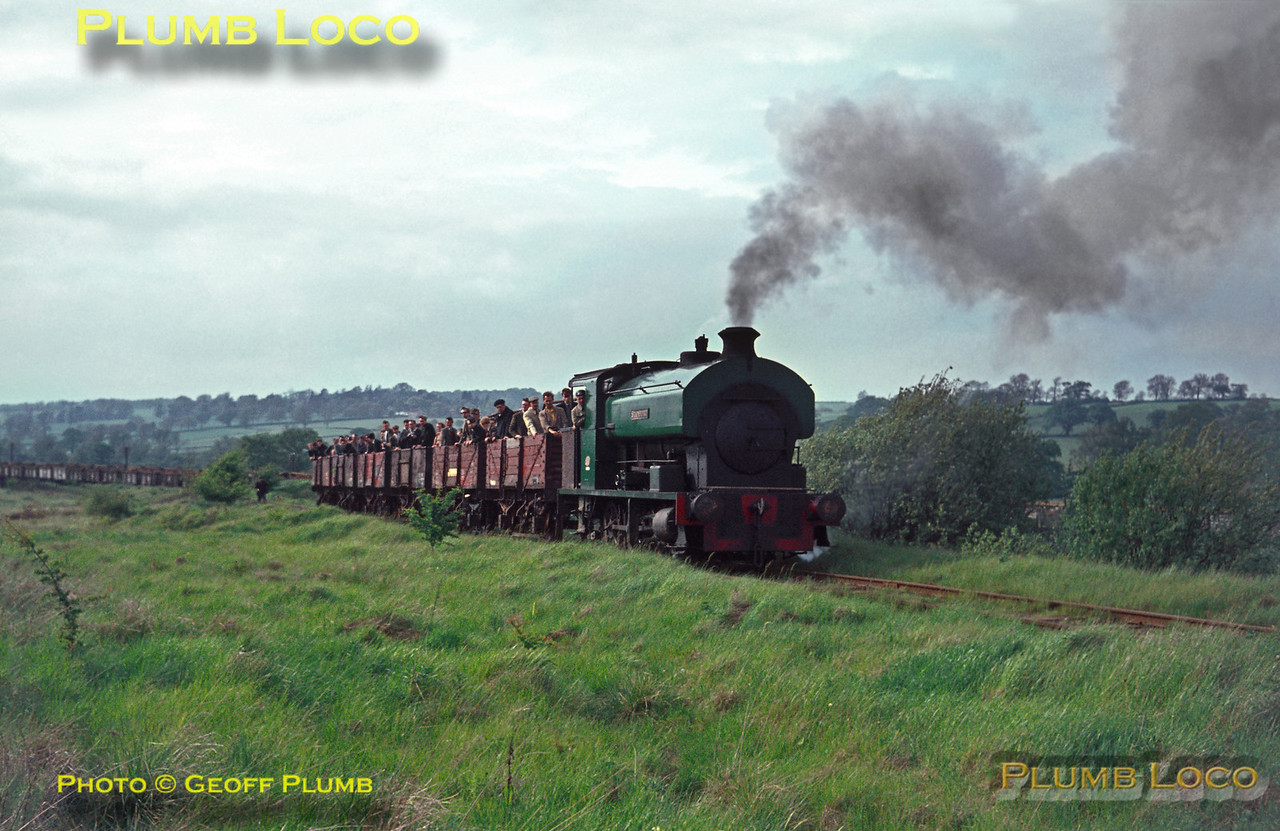 "From the Geoff Plumb Collection of original slides. Members of the Industrial Railway Society fill the open wagons behind Staveley Iron & Steel Co. No. 24 ""Stamford"" as it works up the 1 in 25 gradient away from the exchange sidings with BR at Pilton. This was between Manton and Luffenham on the Midland line from Leicester to Peterborough and the industrial line ran a short distance to the ironstone quarry at Pilton. The loco is an Avonside 0-6-0ST, No. 1972 of 1927 and is still in existence though in very poor condition. Saturday 21st May 1966. Photo courtesy John Edgington. Collect Slide No. 1922."