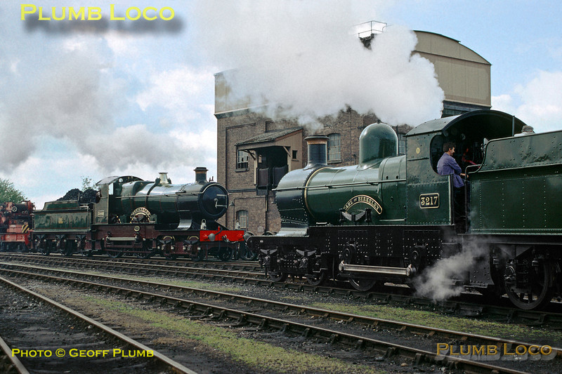 """GWR 4-4-0s were not exactly thick on the ground in 1989, so to get two in one shot - and both in steam - was quite something! On the left is """"City"""" class No. 3440 """"City of Truro"""" preparing to go off shed to work a special train to Stratford-upon-Avon, whilst on the right is """"Dukedog"""" No. 3217 """"Earl of Berkeley"""". Both are at the Didcot Railway Centre, based in the former steam shed on the morning of Saturday 13th May 1989. Slide No. 19832."""