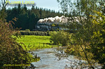 """The River Evenlode is in full spate in one direction while """"Britannia"""" 4-6-2 No. 70013 """"Oliver Cromwell"""" is in full cry in the other direction. It is working hard at the head of 1Z71, """"The Cotswold Venturer"""", 08:05 from Paddington to Worcester via Evesham and return via Sapperton on Saturday 6th October 2012. In glorious, but awkwardly angled, sunlight the train is seen near Lyneham running on time at 11:06. Digital Image No. GMPI12508-2."""