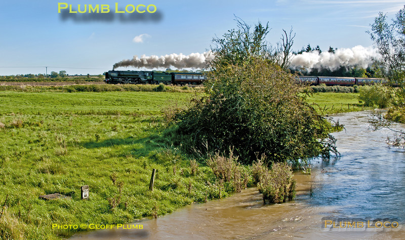 """The River Evenlode is in full spate in one direction while """"Britannia"""" 4-6-2 No. 70013 """"Oliver Cromwell"""" is in full cry in the other direction. It is working hard at the head of 1Z71, """"The Cotswold Venturer"""", 08:05 from Paddington to Worcester via Evesham and return via Sapperton on Saturday 6th October 2012. In glorious, but awkwardly angled, sunlight the train is seen near Lyneham running on time at 11:06. Digital Image No. GMPI12510."""