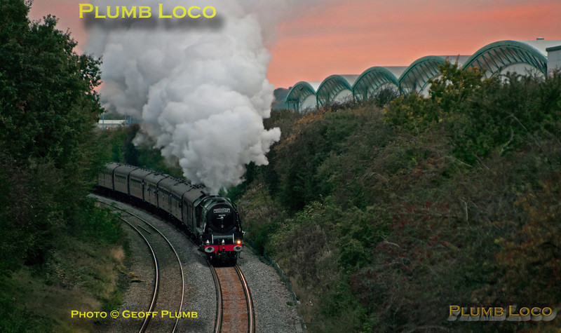 """With the setting sun tingeing the sky, Stanier """"Princess Coronation"""" class 4-6-2 No. 46233 """"Duchess of Sutherland"""" is getting away from the stop for water at Ridgmont station with 1Z87, the 16:13 return from Euston to Sheffield, 17:42, Saturday 20th October 2012. The huge warehouse on the right is on the site of the former brickworks on the Marston Vale line. Digital Image No. GMPI12686."""