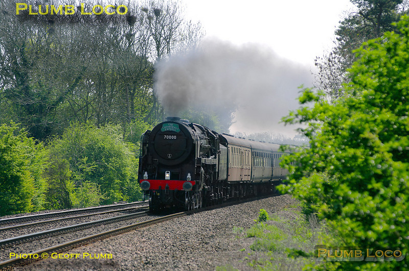 """BR Standard 4-6-2 No. 70000 """"Britannia"""" is hard at work at the head of the 12 coach 1Z40, """"The Cathedrals Express"""", 09:36 from Paddington to Stratford-upon-Avon. It is approaching the foot-crossing at Wormleighton a few minutes early at 12:11 on Saturday 23rd April 2011. This was the hottest day of the year so far, but with the loco working hard and being fired, some visible exhaust is apparent. The loco is still carrying its unlined black livery and is without its nameplates. Digital Image No. GMPI8813."""