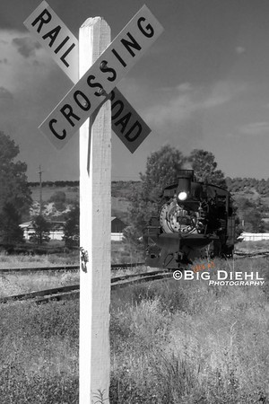 The light locomotive approaches the railroad crossing.