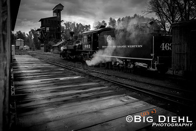 "Awaiting her crew, a lone mudhen sits with her freight train, on the mainline of the Denver and Rio Grande Western's ""San Juan Extension"" under the shadows of Chama's iconic Coal and Water Towers.  A early morning rain shower has soaked the deck of the warehouse platform here."