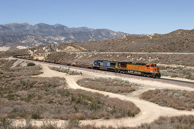 BNSF 5246 (C44-9W) & CSX 7689 (C40-8W) climb past Hill 582 with an eastbound bare table train. 07/05/2007.