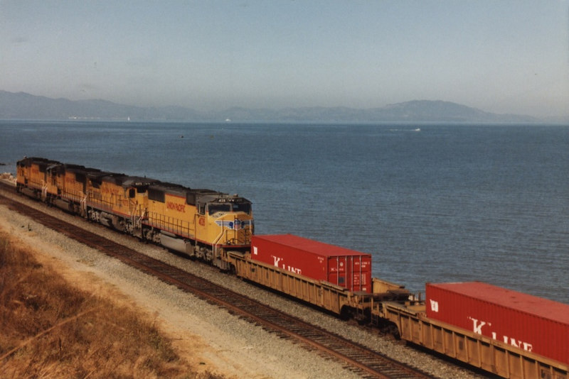 It's a clear day at Pinole and the hills of Marin County are visible across the bay in the background as this UP K Line stacker rolls by.