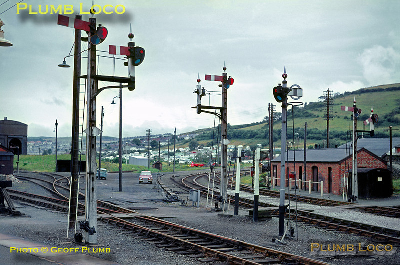 A fine array of lower quadrant semaphore signals adorns the country end of Aberystwyth station, looking towards the engine shed to the left and the lines to Carmarthen curving away to the right. After this line had closed, the narrow gauge Vale of Rheidol Railway was diverted from outside the station area into the Carmarthen line platforms and the standard gauge shed became the narrow gauge depot. August 1966. Slide No. 2457.