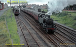 "BR Standard 3MT 2-6-2T No. 82009 starts the up Pwllheli portion of the ""Cambrian Coast Express"" away southwards from Tywyn station with six coaches in tow, whilst in the down siding is 2-6-4T No. 80105 with the pick-up goods bound for Pwllheli, once the road is clear. Wednesday 29th July 1964. Slide No. 873."