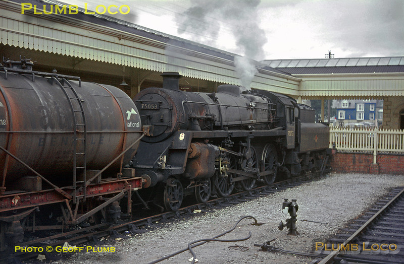 BR Standard 4MT 4-6-0 No. 75053 looks in pretty rundown condition as it sits at the bufferstops with a train of oil wagons in the Carmarthen line bay platforms at Aberystwyth station. After the line to Carmarthen was closed, these platforms remained unused until the narrow gauge Vale of Rheidol tracks were diverted from outside the station building to this area. August 1966. Slide No. 2453.