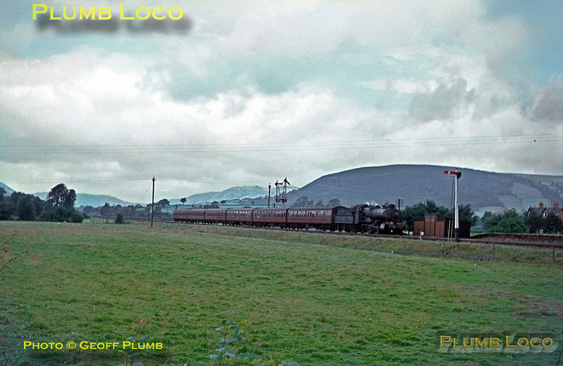 """Manor"" class 4-6-0 No. 7828 ""Odney Manor"" drifts into Caersws station with the up working of ""The Cambrian Coast Express"", from Aberystwyth and Pwllheli to London Paddington on Tuesday 28th July 1964. Slide No. 844."