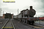Collett GWR 2251 Class 0-6-0 No. 3208 sits out of use at Pwllheli MPD on Saturday 8th August 1964. It had regularly been working the 07:35 from Pwllheli to Machynlleth stopping passenger train and the 18:55 return from Machynlleth up until the previous week, but this train was now in the hands of an Ivatt 2-6-0. At the back of the line of coal wagons is Ivatt 2-6-0 No. 46446 and Standard 3MT 2-6-2T 82006 is in the shed. Slide No. 945.