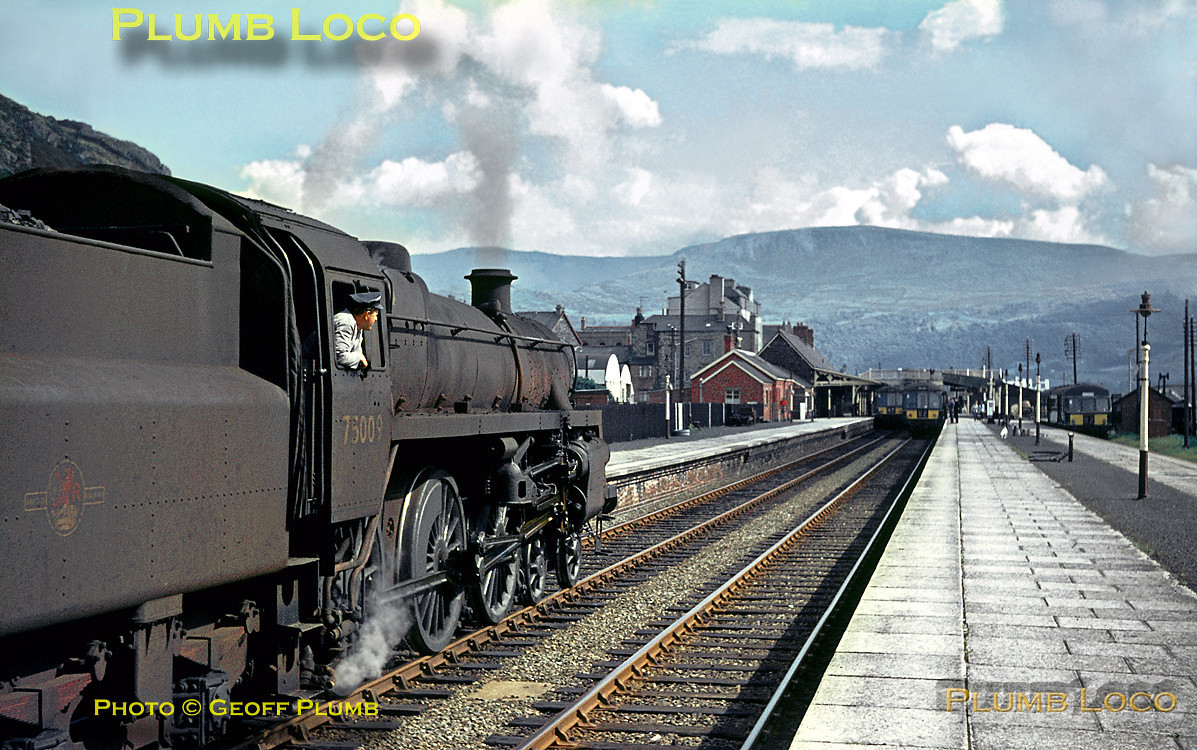 "BR Standard 4MT 4-6-0 No. 75009 is shunting at Barmouth station with the up daily pick-up goods from Pwllheli to Machynlleth. In the station, all tracks are occupied by DMU's which by this time had taken over all the local passenger trains, only the ""Cambrian Coast Express"" was still steam hauled during the week. Summer Saturday extras were also still steam hauled at this stage. The 2928 feet bulk of Cadair Idris dominates the skyline in the background. Monday 22nd August 1966. Slide No. 2493."