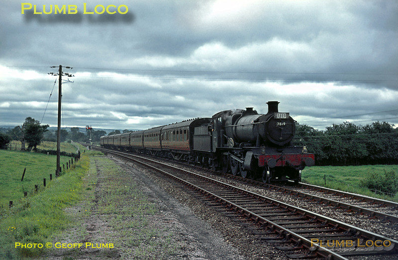 """GWR """"Manor"""" Class 4-6-0 No. 7819 """"Hinton Manor"""" is approaching Welshpool station with the 10:45 train from Aberystwyth to Paddington on Saturday 25th July 1964. The train consists of eight coaches, the maximum allowed for an unassisted """"Manor"""" over Talerddig bank. Slide No. 816."""