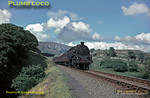 BR Standard 4MT 2-6-4T No. 80136 is at the head of the 08:20 from Paddington to Pwllheli express as it climbs over the hilly section between Porthmadog and Black Rock Sands, the 1181ft bulk of Moel Ddu towering in the background. Saturday 8th August 1964. Slide No. 942.