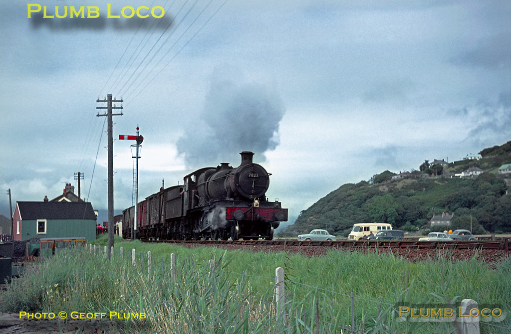 """This was the only occasion that I saw a """"Manor"""" working the goods on the Cambrian line - filthy 7823 """"Hook Norton Manor"""" passes the station and level-crossing at Fairbourne at 16:55 with the afternoon up pick-up goods train from Pwllheli to Machynlleth. An interesting assortment of contemporary road vehicles are waiting at the crossing. Wednesday 29th July 1964. Slide No. 884."""
