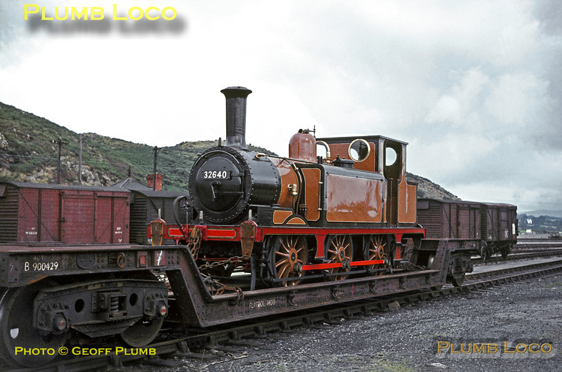 "An unlikely occupant of the goods yard at Pwllheli is ex-LB&SCR A1X ""Terrier"" 0-6-0T No. 32640 which has recently arrived on a well wagon. It has been cosmetically restored to a semblance of LB&SCR livery, though it is still carrying its BR number. It had been purchased by Sir Billy Butlin and had arrived to go on display at the Holiday Camp at Pen-y-Chain, along with Stanier ""Princess Royal"" 4-6-2 No. 46203 ""Princess Margaret Rose"". Both engines have since returned to steam, 32640 on the Isle of Wight Steam Railway as W11 ""Newport"". Saturday 8th August 1964. Slide No. 947."