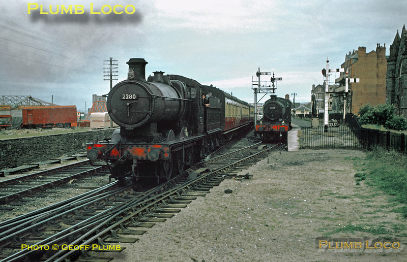 "From the Geoff Plumb Collection of original slides. Collett ""2251"" class 0-6-0 No. 2280 sets off from Barmouth with a local stopping train to Machynlleth with a rake of coaches in ""blood & custard"" livery. It has just passed ""Manor"" 4-6-0 No. 7827 ""Lydham Manor"" which is sitting in the up bay platform between duties. Friday 25th July 1958. Photo by D.E. White. Collect Slide No. 29337."