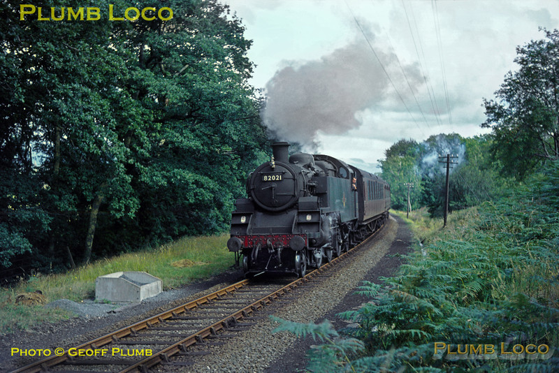 BR Standard 3MT 2-6-2T No. 82021 is in charge of the 08:32 train from Birmingham Snow Hill to Pwllheli, which ran via Ruabon and Dolgellau, here seen soon after leaving Porthmadog, near Penamser, next stop Criccieth, or possibly at Black Roack Sands Halt. Saturday 8th August 1964. Slide No. 940.