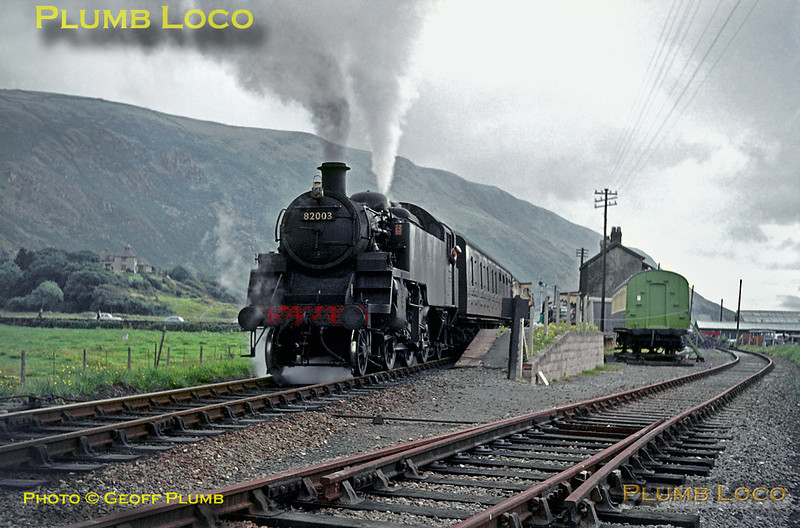 BR Standard 3MT 2-6-2T No. 82003 waits impatiently at Fairbourne station to restart its train, the 15:40 local passenger from Machynlleth to Pwllheli. In the background are Friog cliffs where the line runs through an avalanche shelter above the seashore. Note the camping coach on an isolated track panel, a feature of many seaside stations. Wednesday 29th July 1964. Slide No. 883.