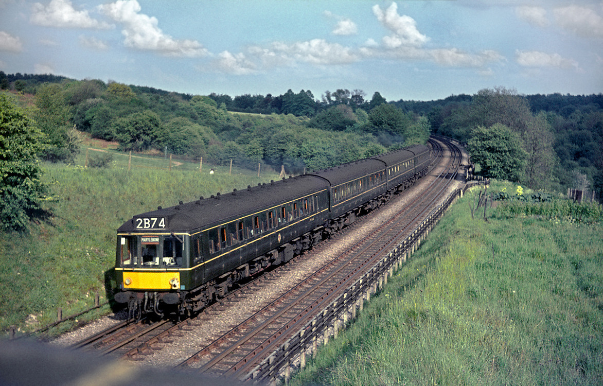 An unidentified Class 115 DMU has just departed from Chorley Wood with the 16:40 train from Aylesbury to Marylebone, heading across the common towards Rickmansworth. Saturday 15th May 1965. Slide No. 1315.