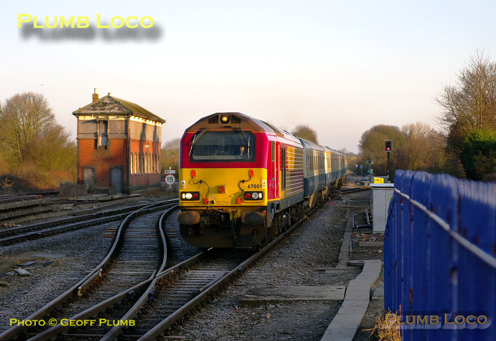 The sun has now climbed a little higher but the temperature is still below freezing as 67001 approaches Princes Risborough for its stop there with 1H08, the 06:53 Chiltern LHCS from Banbury to Marylebone. The train consists of six blue/grey Mk.3 coaches and DVT 82302 on the rear. The train is due to depart here at 07:30 and is on time as it arrives at 07:29 on Monday 7th March 2011. Digital Image No. GMPI8121.