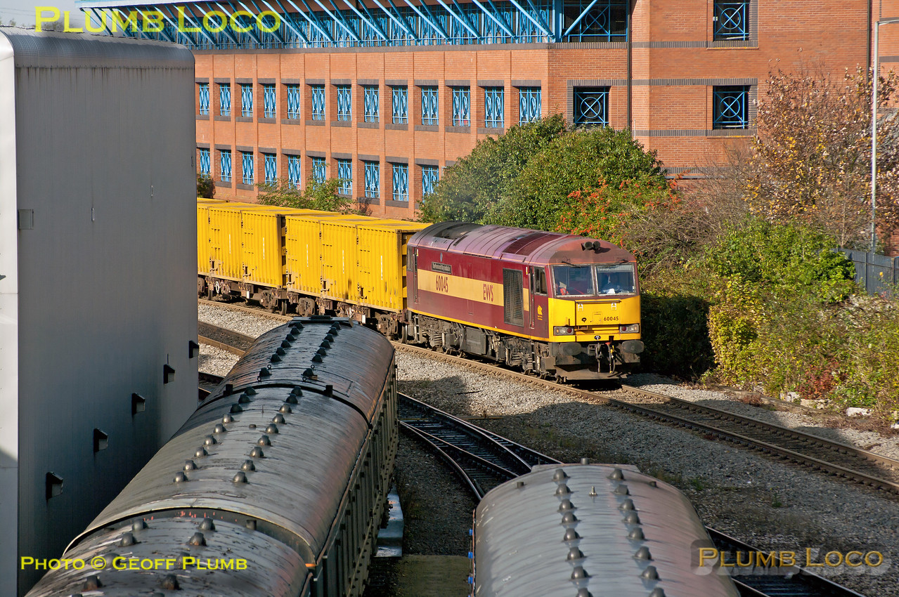 "With both 6A58 and 6V49 scheduled to leave Calvert at the same time, 10:14 to Northolt and Thorney Mill respectively, it was something of a gamble as to which train turned up! In the event, 6A58 won the toss and is seen here passing Aylesbury Depot at 10:54 with 60045 ""The Permanent Way Institution"" in charge, the first time a Class 60 has been around these parts for ages. The loco also carries a 40B (Immingham) shed allocation plate. On the left in the foreground is the ""Green Goddess"" Class 117 Sandite Unit No. 960 301, alongside ""Bubblecar"" 121 020. Tuesday 30th October 2012. Digital Image No. GMPI12749."