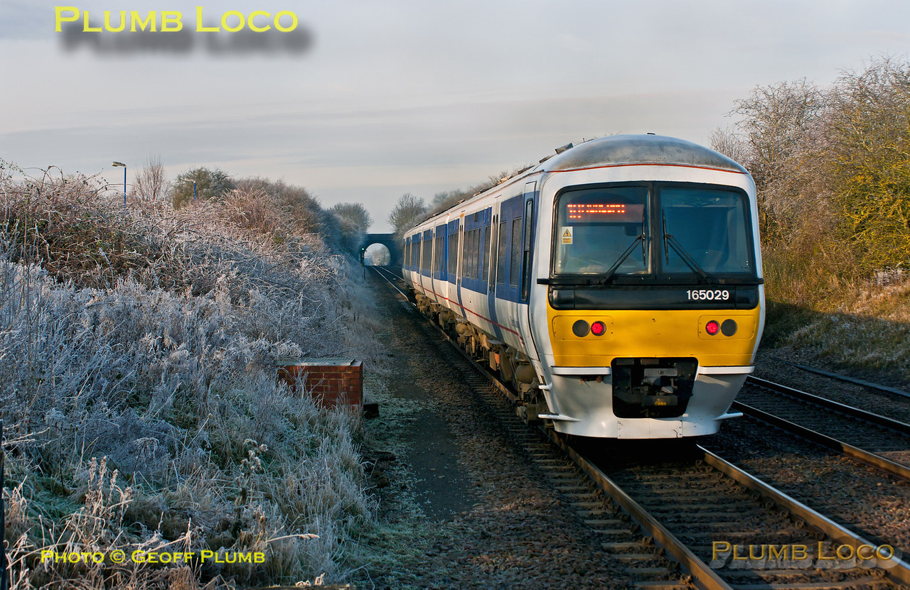 At 12:02 the sun has just passed its highest for the day but the temperature has not risen high enough to melt the frost on the foliage after the previous day and night of freezing fog... 165 029 departs from Haddenham & Thame Parkway station on time with 1U26, the 11:18 from Marylebone to Banbury. Wednesday 12th December 2012. Digital Image No. GMPI13253.