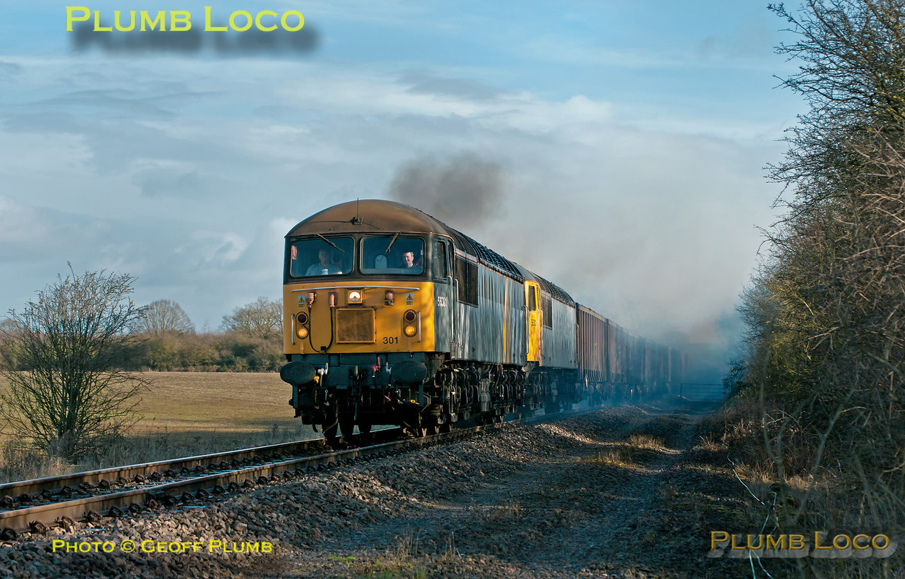 56301 is now leading with failed 56312 behind, but both locos producing voluminous clouds of smoke, as the train approaches Charndon having departed from Claydon L&NE Junction at 11:27, a few minutes earlier than the booked time. It was though 24 hours late as 56312 failed the day before, having got as far as Claydon with 6Z91, the 10:55 fly ash empties from Calvert to Didcot Power Station. 11:28, Tuesday 4th December 2012. Photo taken from a public footpath across the line. Digital Image No. GMPI13110.