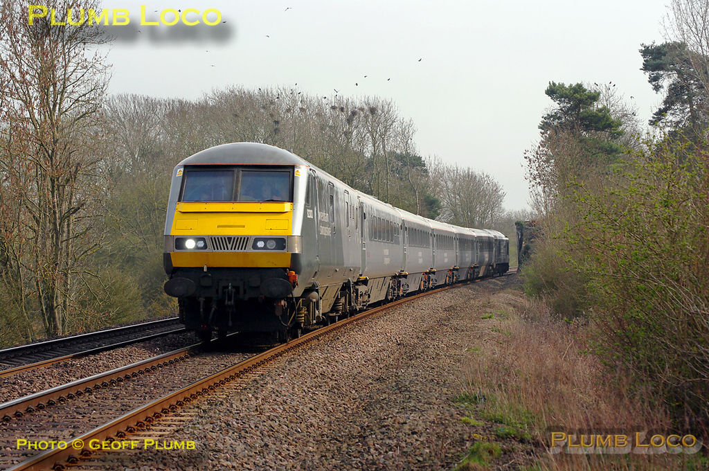 The rooks are busy building their nests in the trees on the old trackbed of the S&MJR line at the point where it formerly bridged the GWR line at Wormleighton as ex-W&S DVT 82303 heads a set of coaches northbound with 67015 on the rear. This was 5R67, 13:43 Marylebone to Birmingham Moor Street driver training run at 15:04 on Tuesday 29th March 2011. Digital Image No. GMPI8338.