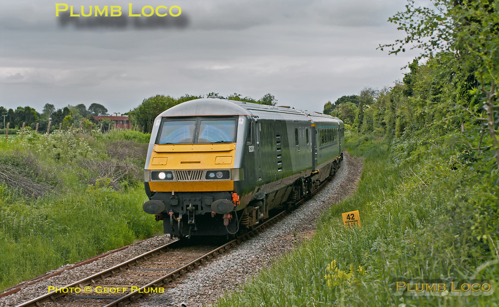 """On a somewhat less than flaming 1st June, a set of the Chiltern """"Silver"""" coaches had been at Aylesbury depot for attention and is now en route back to Wembley LMD. Running as 5F94, 15:00 from Aylesbury, 82301 is leading the set with 67012 on the rear. The train is about to pass Park Mill Farm foot-crossing prior to joining the main line at Princes Risborough. 15:13, Friday 1st June 2012. Digital Image No. GMPI12165."""