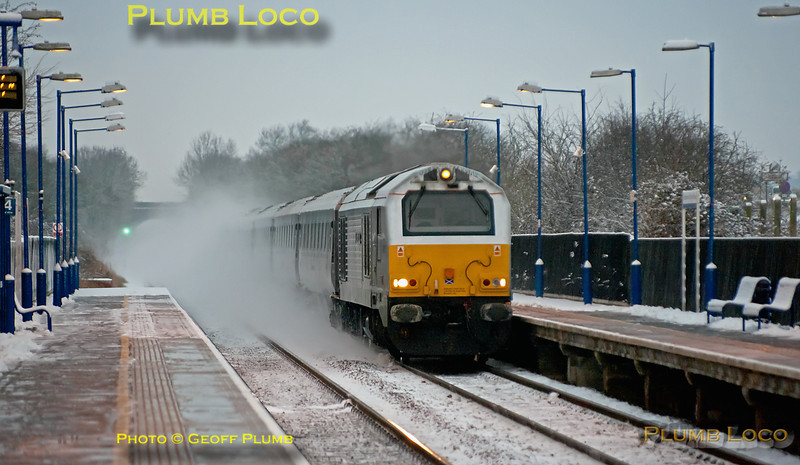 """With its train almost hidden in a cloud of thrown up snow, 67012 """"A Shropshire Lad"""" (I think!) races through Haddenham & Thame Parkway station at the head of 1H09, the 06:19 from Birmingham Moor Street to Marylebone, running just a couple of minutes late at 07:31 on Friday 10th February 2012. Digital Image No. GMPI10970."""