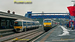 """Under a leaden winter sky, 165 015 departs from Princes Risborough with the 10:10 train to Marylebone, while coming the other way is 82303 at the head of 5T67. This was an ECS move from Wembley LMD at 09:30 to Tyseley for tyre-turning on the Banbury set (AL02), the seven coaches propelled by 67015 """"David J. Lloyd"""". 10:10, Thursday 9th February 2012. Digital Image No. GMPI10931."""