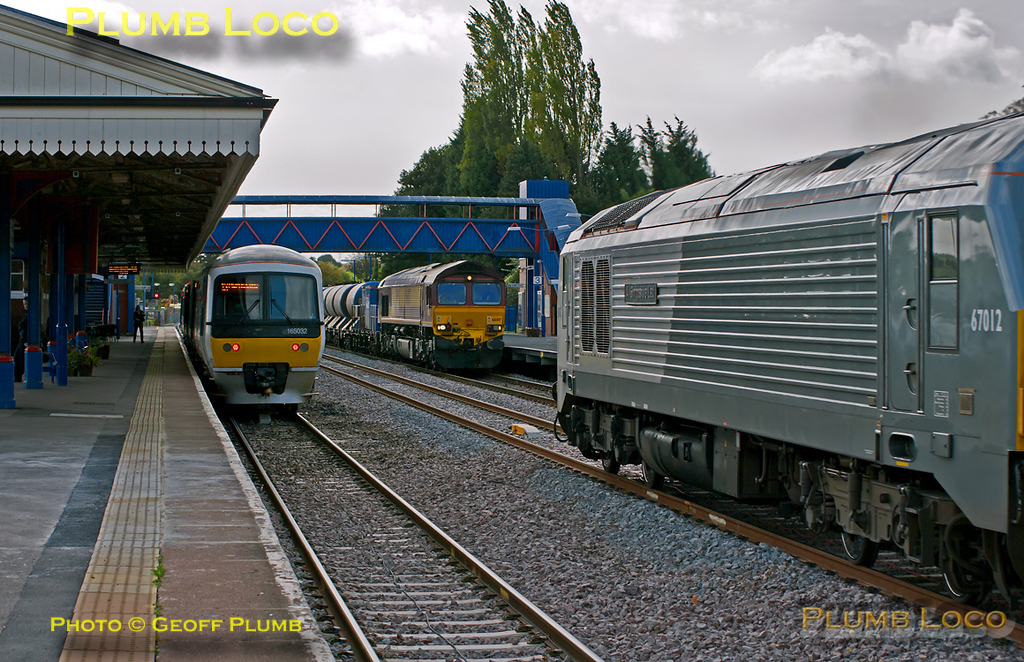 """Full house at Princes Risborough! On the left is 165 032 which had arrived from Marylebone with the 11:13 train which terminates at Risborough at 12:07, in platform 2. It then forms the 12:12 return to Marylebone. In the centre of the picture is 66017 which had arrived a couple of minutes earlier at the head of 3J04, the 11:00 RHTT train from Marylebone with 66001 on the other end of the train. This also terminates at Princes Risborough before returning to Marylebone. On the right is 67012 """"A Shropshire Lad"""" passing through at full linespeed (85mph) with the southbound 1H32, 10:55 from Birmingham Moor Street to Marylebone. 12:09, Thursday 6th October 2011. Digital Image No. GMPI10360."""