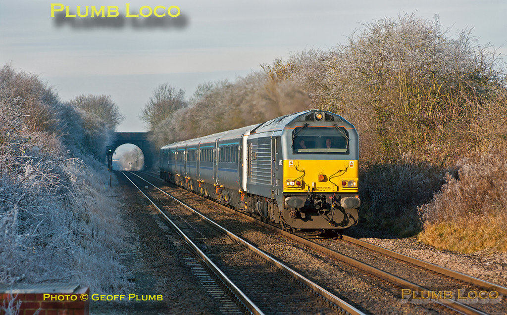 """At one minute past mid-day the sun has reached its zenith but the frost formed by freezing fog the previous day and overnight still has not melted as 67013 """"Dyfrbont Pontcysyllte"""" races southwards approaching Haddenham and Thame Parkway station with DVT 82303 on the rear of the six coaches. This is 1H44, the 10:55 from Birmingham Moor Street to Marylebone on Wednesday 12th December 2012. This set is still the """"wrong"""" way round at the moment with the loco on the south end, though this helps for photography! Digital Image No. GMPI13247."""