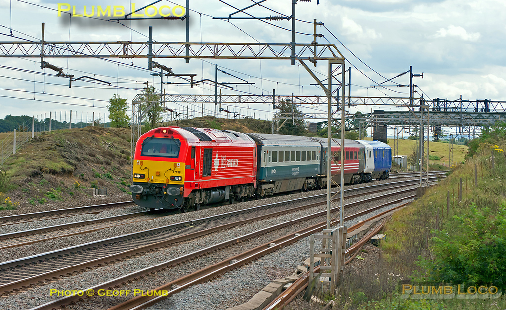 "A train of many colours! During the engineering blockade on the Chiltern line, this was a move from Willesden TMD to Banbury via Coventry, running as 5Z67, 12:00 from Willesden. 67018 ""Keith Heller"" is leading two Mk.3 coaches plus the Chiltern DVT 82302. The coaches are presumably to replace a couple of those at present in set AL02 which normally works the Banbury LHCS turns, but these are not running during the blockade. 12:58, Monday 22nd August 2011. Digital Image No. GMPI10109."