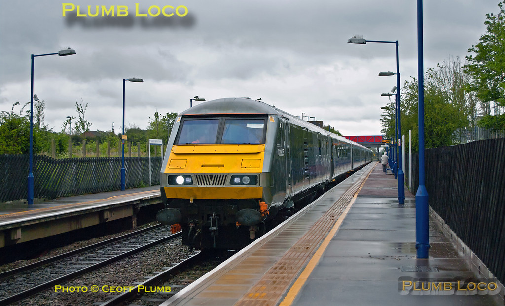 Chiltern DVT 82305 is at the head of 5R00, the 10:59 test train from Wembley LMD to Birmingham Moor Street, with 67014 on the rear of the set. This was the first run of the test train formed of the newly refurbished set of Mk. 3 coaches fitted with power doors, which had worked south from Doncaster the previous Friday. The train is stopping at Haddenham & Thame Parkway station, where onboard staff operated the power doors as part of the training and testing. 12:20, Monday 14th May 2012. Digital Image No. GMPI11680.