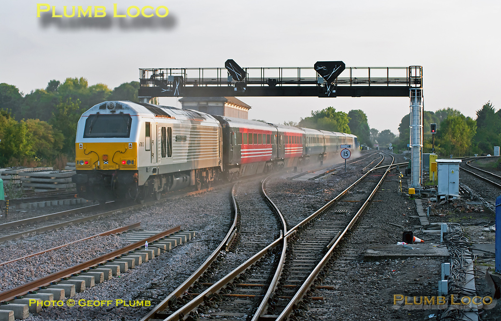 """It's 05:52 and the sun has only just cleared the horizon as 82302 leads 5U08 through Princes Risborough with 67013 """"Dyfrbont Pontcysyllte"""" on the rear of the """"hybrid"""" AL02 set. After the weekend's trackwork, the train almost disappears in a cloud of ballast dust from the newly laid track area. The crossover in the foreground had been severed over the weekend so that the trackbed for the new part of the through line could be prepared and most of the track laid, just a short gap now through which the crossover has been reinstated. There is also one piece of rail missing from the newly connected switch in the distance. Monday 11th July 2011. Digital Image No. GMPI9651."""