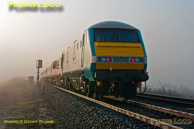 With the temperature only just above freezing and the sun struggling to clear the early morning mist, 82307 (in Arriva Trains Wales livery) is on the rear of 1H08, the 06:53 from Banbury to Marylebone, as it passes the foot-crossing at Launton, 67018 leading the train. 07:10, Friday 13th April 2012. Digital Image No. GMPI11571.
