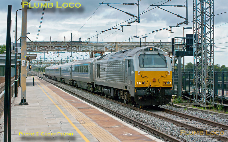 """Chiltern Mainline on the West Coast Main Line! Former WSMR 67014 """"Thomas Telford"""" is at the head of the first set of Chiltern Mainline branded silver coaches with DVT 82305 on the rear of the five coaches, as they pass Cheddington Station. This train, 1I28, was a charter from Birmingham Moor Street to Wembley Stadium for the Community Shield match between Manchester City and Manchester United. Departing from Moor Street at 09:03, the journey was somewhat complicated by engineering works on the Chiltern line, not due to be completed until later in the day. Thus the train ran via reversal (three times!) at Leamington Spa, reversal at Coventry and then up the WCML to Wembley Central. Then a further reversal at Mitre Bridge to Willesden No. 7 for another reversal to Acton Canal Wharf. Here the final reversal took place and the train then ran via the Neasden Curve to arrive at Wembley Stadium from the south (actually, east!), where it was due at 12:14. The return train was due to run via the normal route to Moor Street after the match. 11:08, Sunday 7th August 2011. In the event, the train did not get to Wembley Stadium due to constraints over the use of the projected route. Passengers were detrained at Harrow & Wealdstone to continue their journey by LOROL to Wembley Central. The ECS of the train was then due to stable at Willesden TMD, but was able to run as ECS over the original route, so ended up in Marylebone until required for the evening return run... Digital Image No. GMPI9958."""