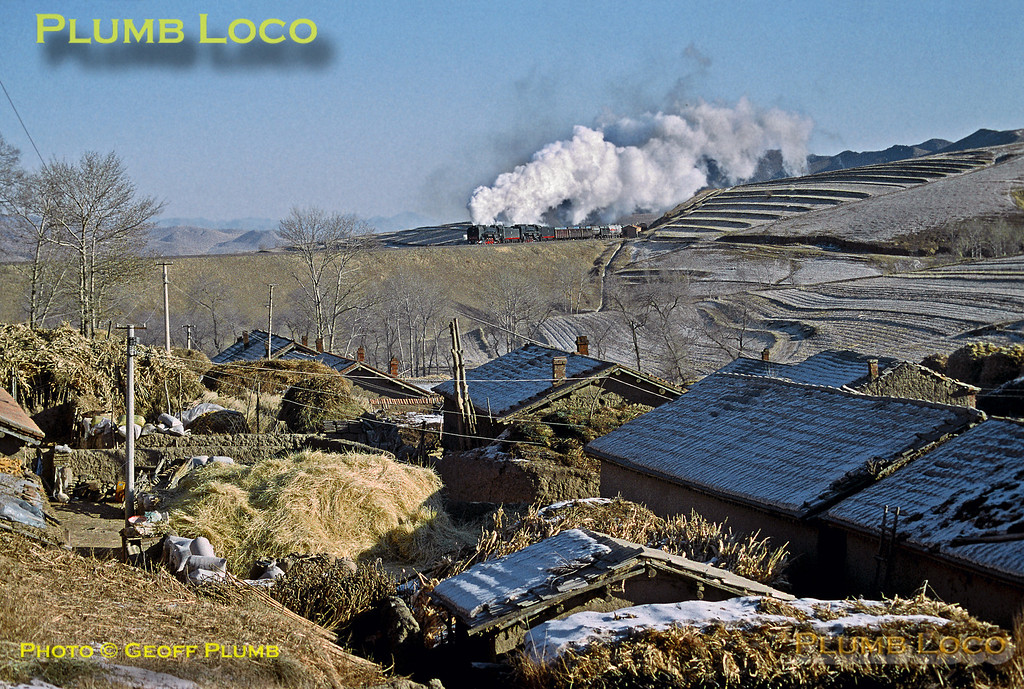QJ class 2-10-2s No. 6110 and 6851 are on the final stages of the westbound climb of the Jing Peng Pass between Liudigou and the summit at Shangdian, passing the small settlement at Nan Di en route. 09:10, Wednesday 13th November 2002. Slide No. 31929.