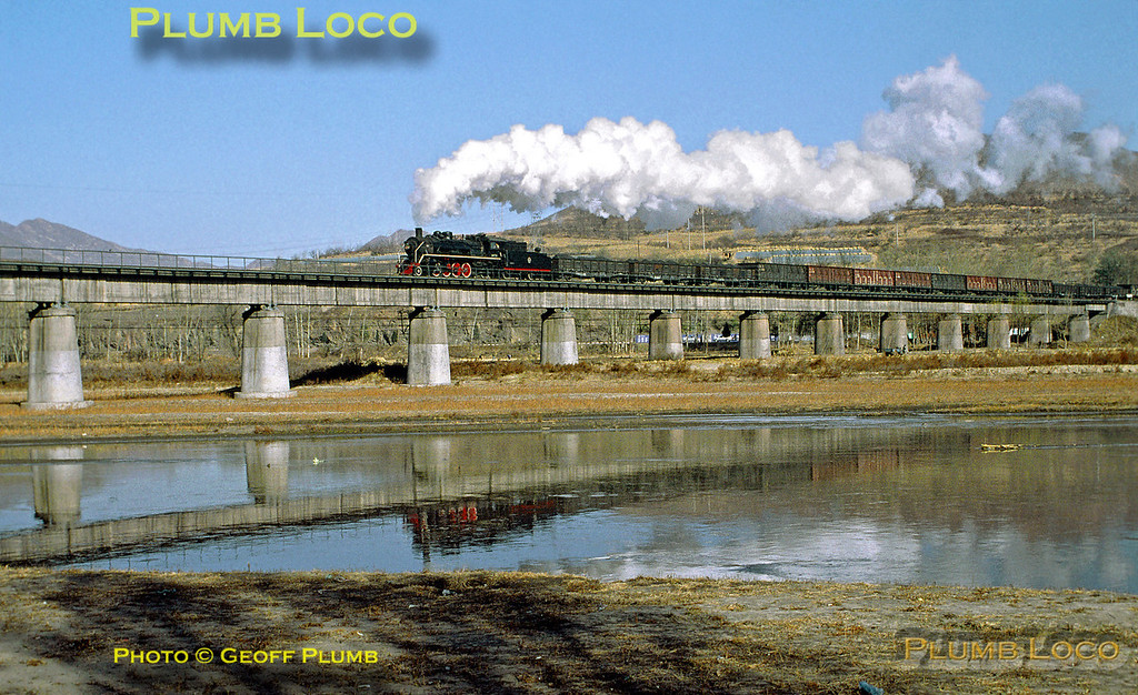 2-8-2 No. SY1726 crosses the river bridge near the steelworks on the branch from Chengde with another loaded coal train, its exhaust steam condensing nicely in the cold air. 10:10, Monday 4th November 2002. Slide No. 30382.