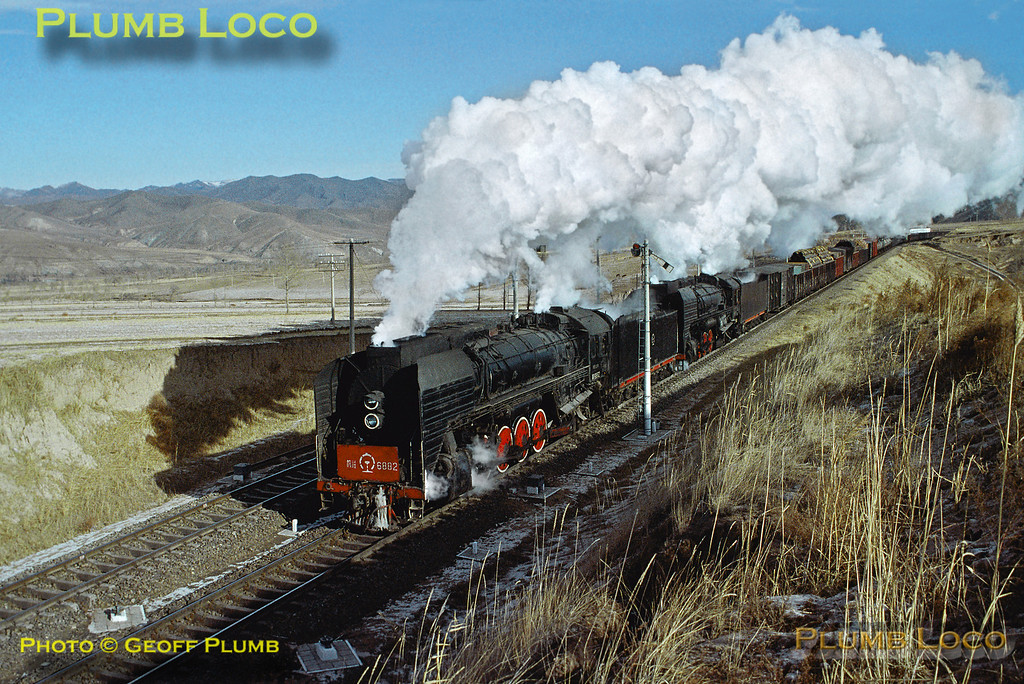 QJ class 2-10-2s Nos. 6882 and 6760 are on the westbound climb of the Jing Peng Pass, passing through Liudigou station with another long freight train, under the control of lower quadrant semaphore signals. 10:17, Wednesday 13th November 2002. Slide No. 31946.