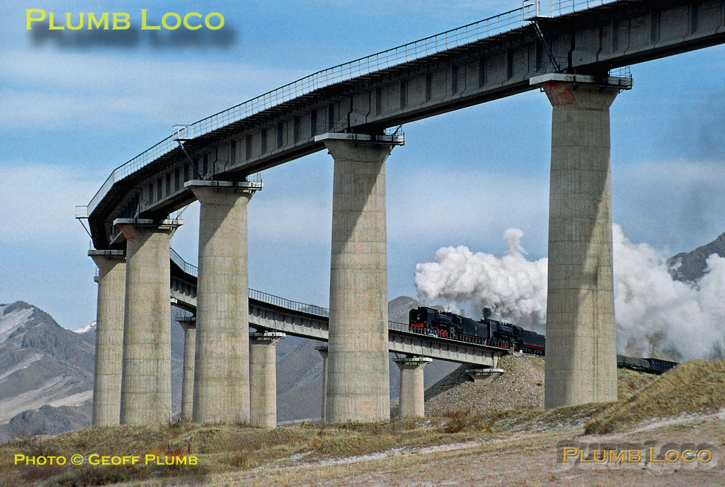 "QJs Nos. 6998 & 6630 are on the eastbound climb of the Jing Peng Pass at Simingyi ""Horseshoe"" Viaduct with train 22829, 09:10 from Haloukou to Daban, Wednesday 13th November 2002. Slide No. 31989."