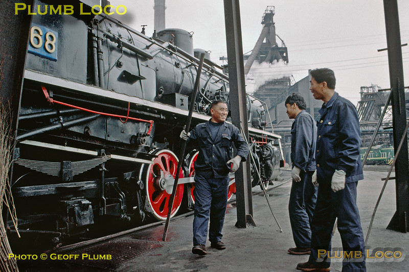 With one of the many blast furnaces towering in the distance, a loco servicing crew enjoy a joke as they go about their duties with 2-8-2 SY1568 at Anshan steelworks, Tuesday 5th November 2002. The railway system here used steam, diesel and electric traction (one of the diesels can be seen in the background). The steel works is vast, covering 37 square kilometres and employing around 200,000 people! Slide No. 30619.