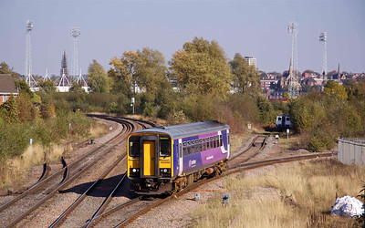 153358 passes Holmes Junction, heading for Sheffield, 29/09/11.  Rotherham's now defunct Millmoor football ground floodlights dominate the skyline
