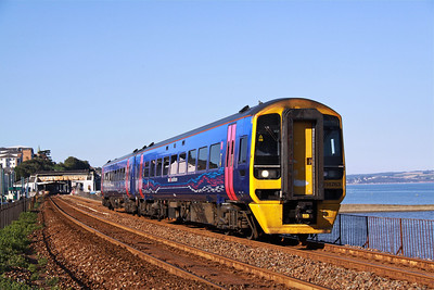 158763, in First Great Western livery, accelerates past the Sea Wall at Dawlish with 2T25, 17:40 Exeter St James Park - Paignton servives on the evening of 24/07/12.