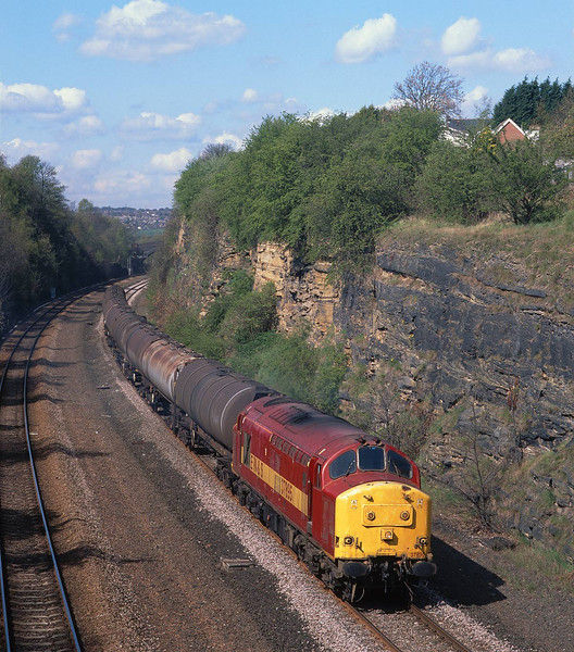 37895 powers away from Healey Mills yard through the delightful location of Horbury Cutting at 11:35 on Tuesday 20th April 2004, with the 6D78 fuel tanks to Neville Hill.