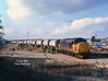 37516 brings a rake of empty and extremely unfamiliar RH Roadstone aggregate hoppers into Hull Coal Terminal at 15:25 on Wednesday 10th March 1999. The train had worked from Toton as 6Z77 to be loaded with a one off consignment of pumice which returned as 6Z78 to Allington.<br /> The access road being crossed by the locomotive leads to the docks New Yard, Saltend Reception sidings and the small wagon repair facility of Marcroft Engineering.<br /> I was incredibly lucky to capture this train at all - I just happened to pass the working as it stormed through Hessle as I was driving out of town on the adjacent A63 - I abandoned my plans!